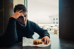 Portrait of a young bearded man sitting in the restaurant and fast food can no longer eat. Portrait of a young bearded man in black sitting in the restaurant and Royalty Free Stock Photo