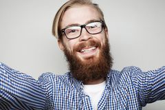 Portrait of young bearded man taking selfie and holding camera. With hands over white background stock photo