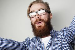 Portrait of young bearded man taking selfie and holding camera. With hands over white background stock photography