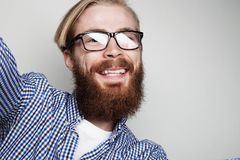 Portrait of young bearded man taking selfie and holding camera. With hands over white background royalty free stock images