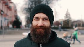Portrait of a young bearded smiling man on the street stock footage