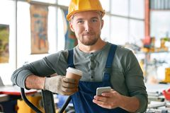 Happy Young Workman on Break. Portrait of young bearded worker taking break in factory workshop looking at camera  while using smartphone holding coffee cup Stock Photography