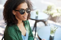 Portrait of young beautiful african girl in sungasses smiling resting relaxing in cafe on terrace. Copy space Stock Photography