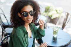 Portrait of young beautiful african girl in sungasses smiling resting relaxing in cafe on terrace. Copy space Royalty Free Stock Photos