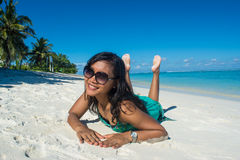 Portrait of young beautiful asian girl laying on her stomach at the beach and smiling at camera Stock Photography