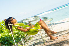 Portrait of young beautiful asian girl relaxing in hammock on tropical beach. Portrait of young beautiful asian smiling girl relaxing in hammock on tropical Stock Image