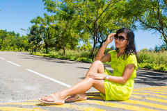 Portrait of young beautiful asian girl sitting on the road looking at camera Royalty Free Stock Images