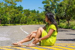 Portrait of young beautiful asian girl sitting on the road looking at side Royalty Free Stock Photo