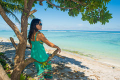 Portrait of young beautiful asian girl sitting in shade under the tree on tropical beach looking at ocean Royalty Free Stock Images