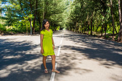 Portrait of young beautiful asian girl standing on the road surrounded by trees Royalty Free Stock Photos