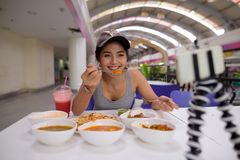 Young beautiful woman vlogging with mobile phone in restaurant. Portrait of young beautiful Asian tourist woman enjoying Indian cuisine at the restaurant in royalty free stock photo