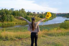 Rear view of young happy Asian woman with sunflowers opening arms against relaxing view of nature royalty free stock photography