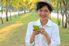 Portrait of young beautiful asian woman and smart phone in hand Royalty Free Stock Photos
