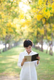 Portrait of young beautiful asian woman standing in yellow flowe Royalty Free Stock Photo