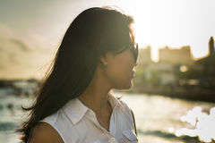 Portrait of a young beautiful asian woman in sunglasses on the city beach during sunset time Royalty Free Stock Photos