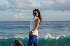 Portrait of a young beautiful asian woman in sunglasses on the city beach during sunset time looking back Stock Photography