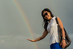Portrait of a young beautiful asian woman in sunglasses holding rainbow in hand Royalty Free Stock Images
