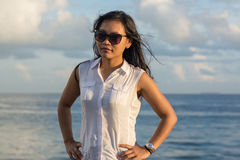 Portrait of a young beautiful asian woman in sunglasses with ocean at background Stock Images