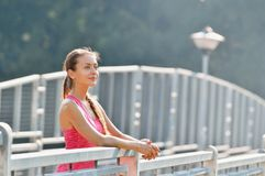 Portrait of young woman smiling on urban metal city bridge after running workout royalty free stock photography