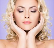 Portrait of young and beautiful blond girl with curly hair. Face lifting and beauty concept. stock photography