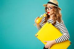 Portrait of young beautiful blond woman in hat with yellow suitc Royalty Free Stock Image