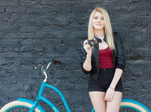 Portrait of a young beautiful blonde girl in a black jacket and shorts posing near the brick wall next to a bright blue vintage bi Stock Photography