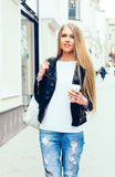 Portrait of a young beautiful blonde girl walking on the streets of Europe with coffee. Outdoor. Warm color. Stock Photography