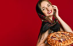 Portrait of a young beautiful blonde in headscarf holding a delicious homemade cherry pie. stock photography