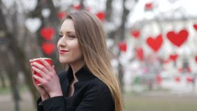 Portrait of young beautiful blonde hipster woman posing on the autumn park background and drinking cup of takeaway stock video
