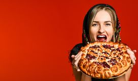Portrait of a young beautiful blonde holding a delicious homemade cherry pie. stock image