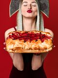 Portrait of a young beautiful blonde in kokoshnik holding a delicious homemade cherry pie. stock photo