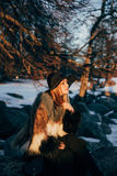 Portrait of a young beautiful blonde woman with hat, in a fur coat, outside, on the snow. A good dark day with beautiful shadows - a sunny winter day, sunset Royalty Free Stock Photos