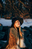 Portrait of a young beautiful blonde woman with hat, in a fur coat, outside, on the snow Stock Image