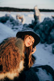 Portrait of a young beautiful blonde woman with hat, in a fur coat, outside, on the snow Stock Photos