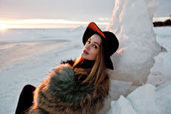 Portrait of a young beautiful blonde woman with hat, in a fur coat, outside, on the snow Royalty Free Stock Images