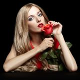 Portrait of young beautiful blonde woman in red dress with red r. Portrait of young beautiful blonde woman in red dress sitting at black table with red rose in Royalty Free Stock Image