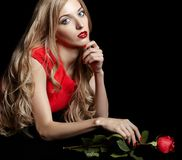 Portrait of young beautiful blonde woman in red dress with red r. Portrait of young beautiful blonde woman in red dress sitting at black table with red rose in Stock Image