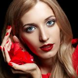 Portrait of young beautiful blonde woman in red dress with red r. Ose in hands on black background Stock Photo