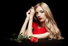 Portrait of young beautiful blonde woman in red dress with red r. Portrait of young beautiful blonde woman in red dress sitting at black table with red rose in Royalty Free Stock Photo