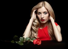 Portrait of young beautiful blonde woman in red dress with red r. Portrait of young beautiful blonde woman in red dress sitting at black table with red rose in Royalty Free Stock Images
