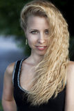 Portrait of young beautiful blonde woman smiling outdoors Stock Photo