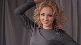 Portrait of young beautiful blonde woman turning head and smiling at camera. stock video