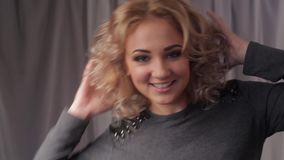 Portrait of young beautiful blonde woman turning head and smiling at camera. stock video footage