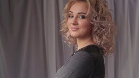 Portrait of young beautiful blonde woman turning head and smiling at camera. Hd stock video