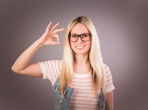 Portrait of young beautiful blonde woman who showing sign `cool` and smiling against the grey background royalty free stock images