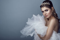Portrait of young beautiful bride in diadem with naked shoulders clasping fluffy skirt of her wedding dress to her breast Stock Images