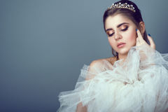 Portrait of young beautiful bride in diadem pressing fluffy skirt of her wedding dress to her breast Royalty Free Stock Image