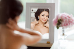 Portrait of the young beautiful bride looks at herself in the mirror Royalty Free Stock Photos