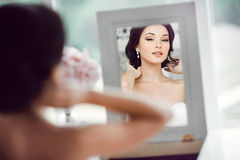 Portrait of the young beautiful bride looks at herself in the mirror Royalty Free Stock Photography