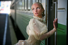 Portrait of young beautiful bride near the train Royalty Free Stock Image